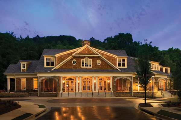 Large Clubhouse lit up at night with prominent circular driveway at One River Place